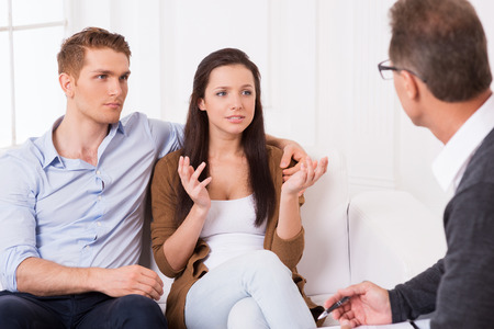 They need an expert advice. Frustrated young couple telling about their relationship problems to psychiatrist  photo
