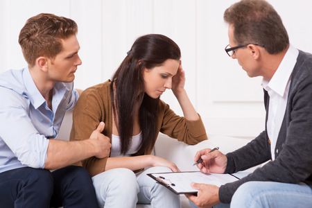 Sentimientos de desesperanza. Hombre joven que consuela a su esposa deprimida mientras está sentado junto a un psiquiatra Foto de archivo