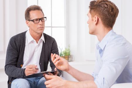 dos personas platicando: La consulta con expertos. Dos hombres que hablan mientras que uno de ellos escribiendo algo en el portapapeles