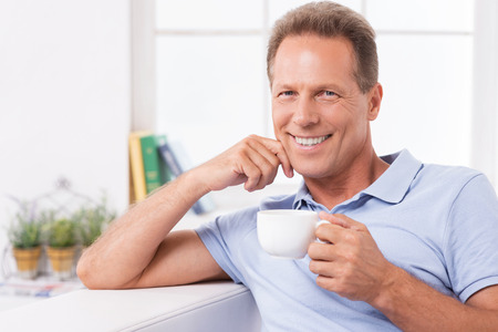fresh news: Relaxing with fresh coffee and latest news. Cheerful mature man drinking coffee and reading newspaper while sitting on the couch at home