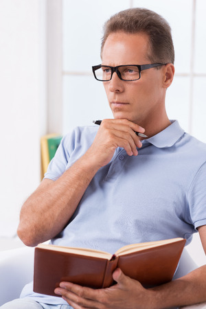 i pad: I need some fresh ideas. Thoughtful mature man holding note pad and touching his chin with pen while sitting on the chair Stock Photo