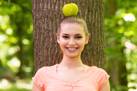 In harmony with nature. Beautiful young woman carrying apple on head and looking at camera with smile while leaning at the tree in a park photo