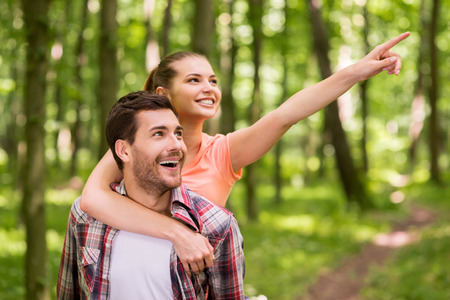 Just look over there! Happy young loving couple walking in park while woman hugging man and pointing away with smile photo