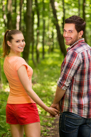 hands holding tree: Good day to walk in park. Beautiful young loving couple walking in park and holding hands