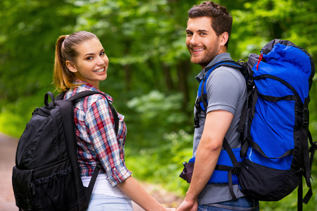 Happy tourist couple. Beautiful young loving couple carrying backpacks and looking over shoulder with smile while walking along the forest pathway photo