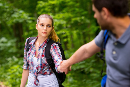expressing negativity: Tired young woman with backpack holding her boyfriend hand and expressing negativity while walking in forest