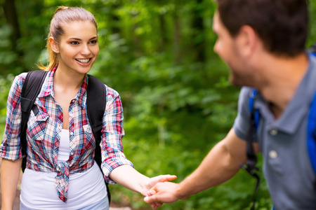 holding hands while walking: Happy young loving couple carrying backpacks and holding hands while walking along the forest  Stock Photo