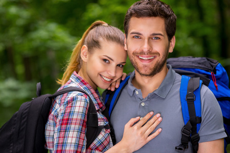 Traveling together is fun. Beautiful young loving couple with backpacks looking at camera and smiling while standing in nature photo