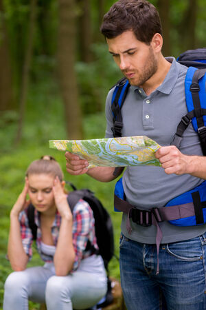 Stuck somewhere in the forest. Thoughtful young man with backpack examining map in forest while woman sitting in the background and holding head in hand photo