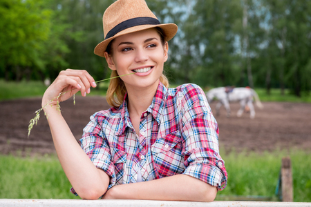 animal mouth: Beautiful cowgirl. Beautiful young woman in cowboy hat looking away and smiling while standing on ranch with horse walking in the background