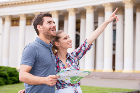 City travelers. Happy young tourist couple standing near beautiful building while man holding map and woman pointing away photo