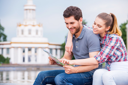 Choosing the place to go next. Happy young tourist couple sitting near beautiful building and examining map together photo