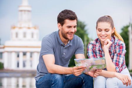 Choosing the place to go. Happy young tourist couple sitting near beautiful building and examining map together photo
