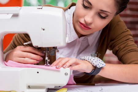 sewing item: She is an expert tailor. Confident female fashion designer working on sewing machine while sitting at her working place Stock Photo