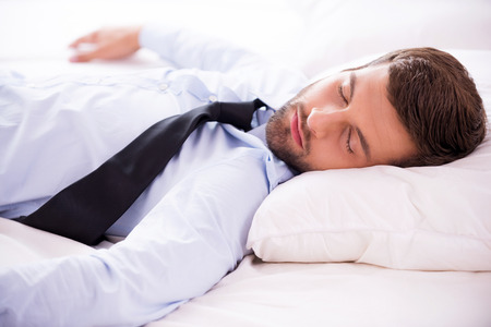 Feeling exhausted after day working. Handsome young man in shirt and tie sleeping in bed  photo