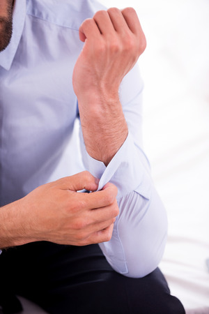buttoning: Adjusting shirt sleeves. Close-up of man in blue shirt adjusting sleeve while sitting on the sofa Stock Photo