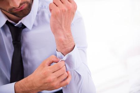 Adjusting shirt sleeves. Close-up of man in blue shirt adjusting sleeve while sitting on the sofa photo