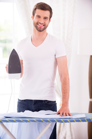 Ironing shirt. Handsome young man holding iron and smiling while standing near the ironing board at home  photo