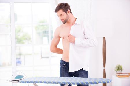 vistiendose: El uso de su camiseta favorita. Hombre joven confidente vestirse camisa blanca después de planchar mientras está de pie cerca de la mesa de planchar