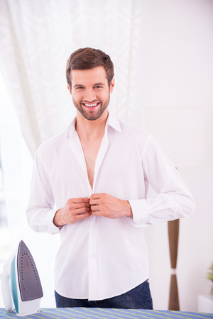 Wearing shirt after ironing. Cheerful young man wearing white shirt after ironing and smiling while standing near the ironing board photo