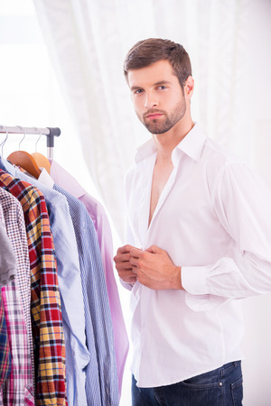 buttoning: Man wearing white shirt. Confident young man dressing up white shirt and looking at camera