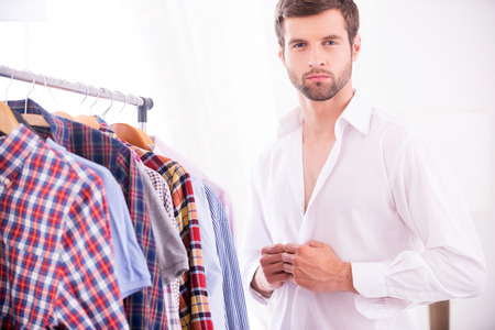 buttoning: Stylish and elegance. Handsome young man dressing up white shirt and looking at camera