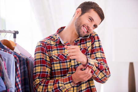 buttoning: Wearing his favorite shirt. Handsome young man wearing shirt and talking on the mobile phone Stock Photo
