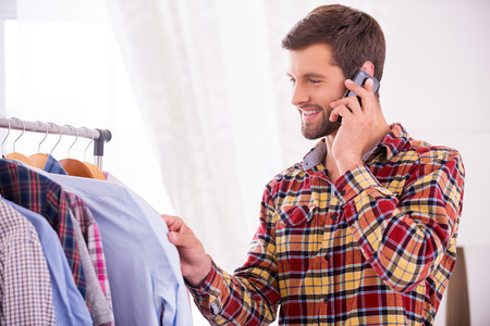 choosing clothes: Choosing shirt to wear. Handsome young man choosing shirt to wear and talking on the mobile phone