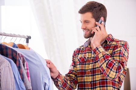 vistiendose: La elección de la camisa al desgaste. Apuesto joven la elección de la camisa al desgaste y hablando por el teléfono móvil Foto de archivo