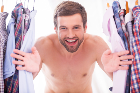 buttoning: Shirts on every day. Happy young shirtless man looking through a various shirts hanging on hangers and smiling  Stock Photo