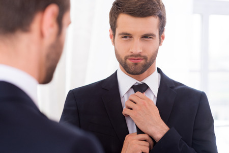 Looking just perfect. Handsome young man in formalwear adjusting his necktie and smiling while standing against mirror photo