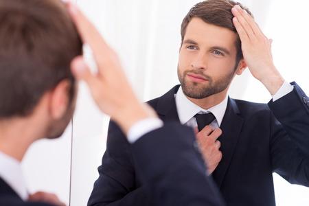 확실히 그는 완벽한 모양 만들기. 정장이 자신의 헤어 스타일을 조정하고 거울에 서있는 동안 웃 고 잘 생긴 젊은 남자 스톡 콘텐츠