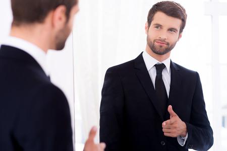 Joven y exitoso. Apuesto joven en traje completo que apunta a sí mismo y sonriendo mientras está de pie contra el espejo