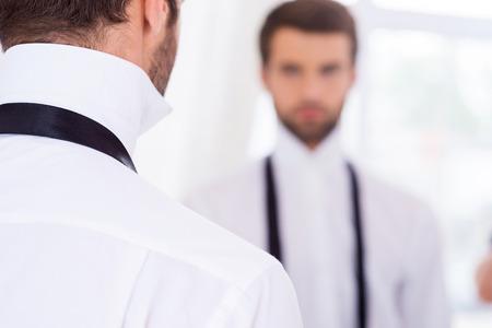 untied: C�mo prepararse para un d�a especial. Vista trasera de un joven con la camisa blanca y la corbata desatada de pie contra el espejo