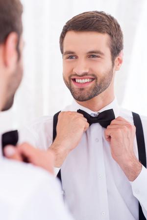 noeud papillon: Marié heureux. Close-up d'un jeune homme en chemise blanche ajustant sa cravate d'arc et souriant tout debout contre miroir