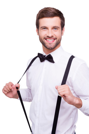 Happy groom. Portrait of handsome young man in white shirt and bow tie adjusting his suspenders and smiling at camera while standing isolated on white