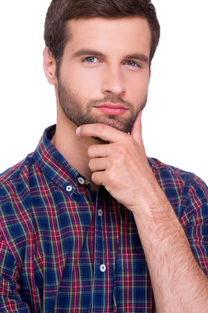 Generating fresh ideas. Portrait of thoughtful young man in casual shirt holding hand on chin and looking at camera while standing isolated on white photo