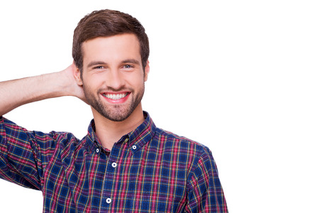 arms behind head: Casually handsome. Portrait of handsome young man in casual shirt holding hand behind head and smiling while standing isolated on white Stock Photo