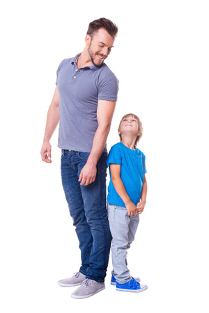 Cheerful father and son. Father and son standing back to back and looking at each other while standing isolated on white