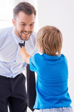 ni�os vistiendose: Asegurarse de que su padre se ve bien. Ni�o juguet�n ayudando padre atar una corbata Foto de archivo