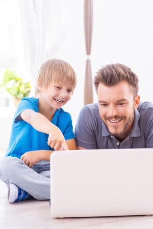 net surfing: Passare del tempo insieme. Buon padre e figlio, navigare in rete a casa mentre piccolo ragazzo che punta monitor portatile e sorridente