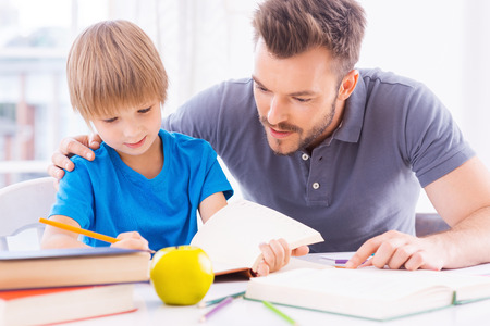 Helping son with homework. Confident young father helping his son with homework while sitting at the table together  photo