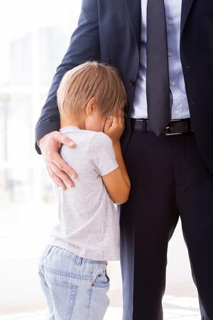 niño llorando: Yo be missing you! El niño pequeño llorando y que cubre la cara con las manos mientras su padre en formalwear consolándole
