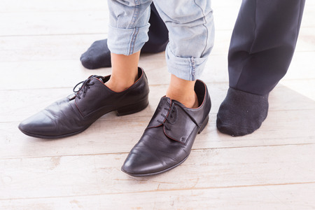 men socks: Close-up of child wearing large shoes while his father standing in socks near him