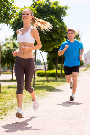 sports track: I am winning!  Cheerful young woman jogging along the road with man  Stock Photo