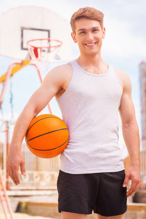 college basketball: Basketball player. Handsome young male basketball player standing outdoors and smiling