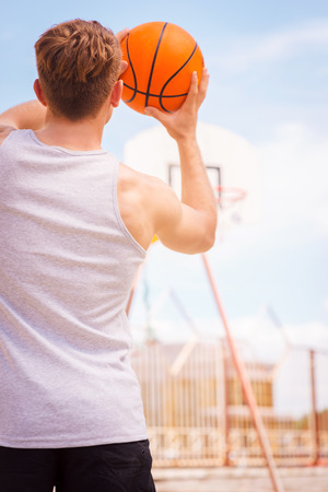 Playing Basketball. Rear view of young male basketball player ready for the shot photo