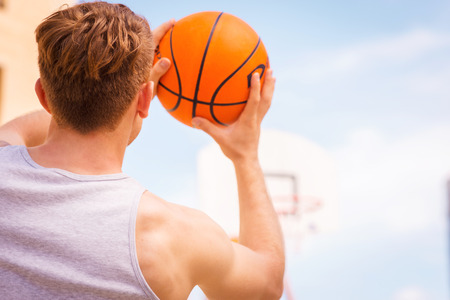 Basketball shooting action. Rear view of young male basketball player ready for the shot photo