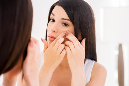 Woman examining face. Beautiful young woman examining her face while looking at the mirror photo