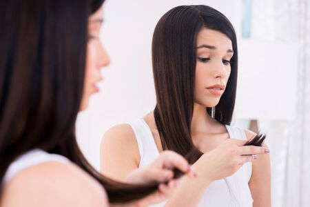 expressing negativity: Examining her damaged hair. Frustrated young woman looking at her hair and expressing negativity while standing against mirror